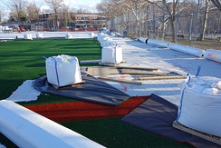 Artificial turf being installed on a baseball field in Queens, New York City.