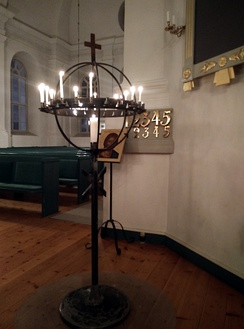 A votive candle rack stands before an icon of Christ Pantocrator in a Luthearn parish church of the Church of Sweden in Skellefteå.