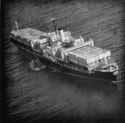Aerial photograph during the boarding SS Mayagüez, note Cambodian gunboats alongside the ship.