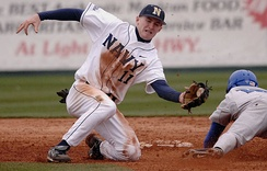 A shortstop tries to tag out a runner who is sliding headfirst, attempting to reach second base.