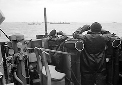 Royal Navy officers on the bridge of a destroyer on convoy escort duties keep a sharp look out for enemy submarines during the Battle of the Atlantic, October 1941