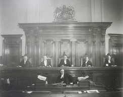 Justices of the Supreme Court of Ontario, with the court clerk seated below the bench. Documents and other forms are evidence is passed to the clerk before being handed to the judge.