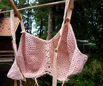 Crocheted pink bra from the 1940s on a clothes line