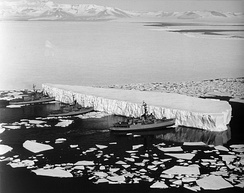 An iceberg being pushed out of a shipping lane by (L to R) USS Burton Island (AGB-1), USS Atka (AGB-3), and USS Glacier (AGB-4) near McMurdo Station, Antarctica, 1965