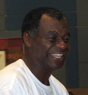 A black person, wearing white t-shirt, is smiling and looking to the right.