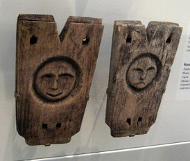 Nunivak Cup'ig kayak cockpit stanchions (ayaperviik). The smiling face of a man and the frowning face of a woman grace these pieces from a kayak frame. Collection of the University of Alaska Museum of the North