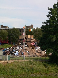 Ulster loyalists prepare to burn the Irish flag on a bonfire on the eve of The Twelfth in Belfast; in some cases they have burned Ivorian flags (erroneously mistaking them for Irish ones).