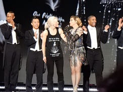 Madonna standing onstage speaking with an audience member, flanked by her dancers in coattails.