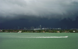 Black rain clouds darken the sky over tropical waters with the city of Miami in the background.