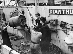 Loading a drum-type Mark VII depth charge onto the K-gun of the Flower-class corvette HMS Dianthus