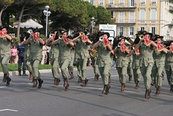 An Italian Bersaglieri fanfare band. As they lack percussion instruments, the band marches at a jogging pace.