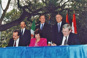Back row, left to right: Mexican President Carlos Salinas de Gortari, U.S. President George H. W. Bush, and Canadian Prime Minister Brian Mulroney, at the initialing of the draft North American Free Trade Agreement in October 1992. In front are Mexican Secretary of Commerce and Industrial Development Jaime Serra Puche, United States Trade Representative Carla Hills, and Canadian Minister of International Trade Michael Wilson.