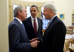 US President Barack Obama discussing the earthquake with former Presidents George W. Bush and Bill Clinton