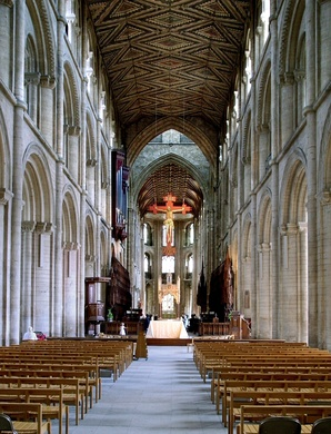 The nave of Peterborough Cathedral (1118–1193) in three stages of arcade, gallery & clerestory, typical of Norman abbey churches. The rare wooden ceiling retains its original decoration (c. 1230). Gothic arches beneath tower (c. 1350).