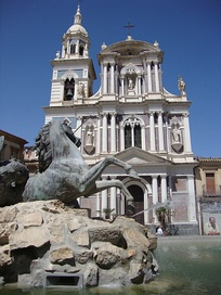 The façade of the Church of San Sebastiano in the foreground with the Triton Fountain.