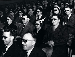 "An audience wearing special glasses watch a 3D ""stereoscopic film"" at the Telecinema"