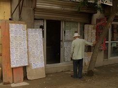 A customer perusing real estate listings at an agent's office in Linxia City, China