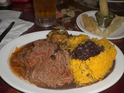 A traditional meal of ropa vieja (shredded flank steak in a tomato sauce base), black beans, yellow rice, plantains and fried yuca with beer