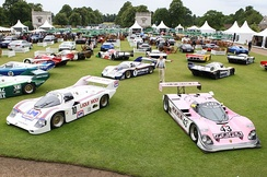 Derek Bell with a number of the Porsche 956s and 962s he drove during his racing career