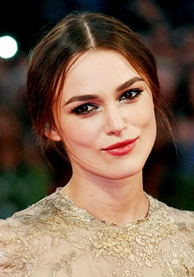 A portrait of Keira Knightley, wearing black tied-up hair, red lipstick, and a gold dress.