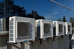 An array of air conditioners outside a commercial office building
