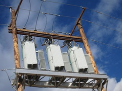 A three-phase bank of voltage regulators used to control the voltage on long AC power distribution lines.  This bank is mounted on a wooden pole structure. Each regulator weighs about 1200 kg and is rated 576 kVA.