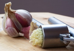 Garlic being crushed using a garlic press