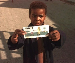 A Somali boy holding up a leaflet dispersed during Operation Restore Hope in the early 1990s
