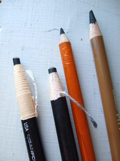 Two charcoal pencils in paper sheaths that are unwrapped as the pencil is used, and two charcoal pencils in wooden sheaths