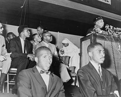 Ali (seen in background) at an address by Elijah Muhammad in 1964