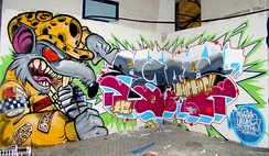 Hip hop-style graffiti showing stylized, elaborate lettering and colorful cartoons.