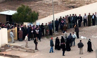 Voters lining up outside a Baghdad polling station during the 2005 Iraqi election. Voter turnout was considered high despite widespread concerns of violence.