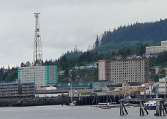 The West End (or Westend), located in the valleys of Carlanna and Hoadley creeks and across Tongass Narrows from Ketchikan International Airport, is Ketchikan's largest commercial and residential area. Shown are the city's tallest buildings, the Marine View Building and Tongass Towers. Ketchikan High School is partially visible at upper right.