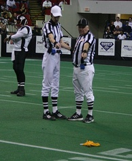 Officials point at a penalty flag lying on the field.