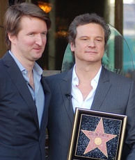 Two middle aged men stand side by side wearing suits and open-necked shirts. One is holding the plaque of a Hollywood star of fame