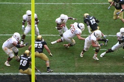 Vince Young of the Texas Longhorns (ball carrier in top center) rushing for a touchdown. A portion of the end zone is seen as the dark strip at the bottom. The vertical yellow bar is part of the goal post.