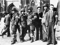 Members of the Dutch Resistance, identified by their cloth armbands, with American paratroopers of the 101st Airborne Division in Eindhoven, September 1944