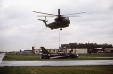 A Sikorsky HH-53C Super Jolly Green Giant helicopter from the 67th Aerospace Rescue and Recovery Squadron lifts a derelict former Royal Air Force BAC Lightning fighter at RAF Woodbridge, Suffolk (UK), on 18 December 1987.