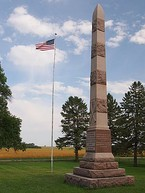 A tall stone spire to the right of a U.S. flag on a pole