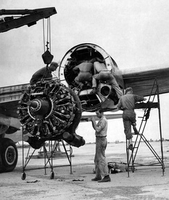 A U.S. Army Air Forces maintenance personnel in India removing a damaged Wright R-3350-23 Duplex-Cyclone engine from a Boeing B-29 Superfortress. They took off any undamaged parts and reused them on the replacement engine (c. 1944–1945).