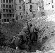 Soviet soldiers running through trenches in the ruins of Stalingrad