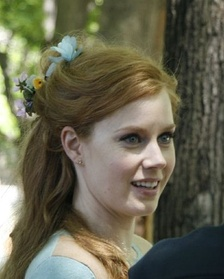 Casual head shot of blue-eyed young woman with long reddish-blond hair pulled back.