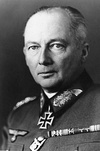 Black-and-white portrait of an older man wearing a military uniform with an Iron Cross displayed at his neck, his hair is combed back.