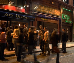 Irish teenagers over 18 hanging around outside a bar. People under 18 are not allowed to drink outside the home; this is not strictly enforced in Ireland.