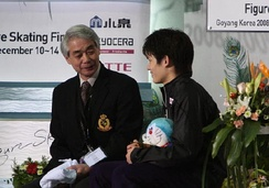"Takahiko Kozuka waits for his marks with coach Nobuo Sato in the ""Kiss and cry"" area"