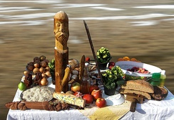 A table on which fruits and some wooden icons are situated