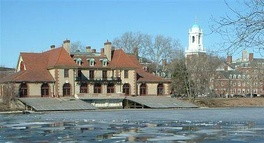Weld Boathouse from the Charles River, with Harvard University buildings visible in the background and the partially frozen Charles River in the foreground