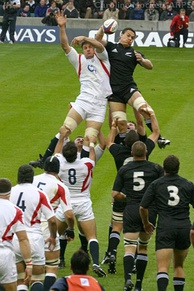 The All Blacks and England contesting a line-out. Both sets of forwards lined up wearing white and black respectively, with a player from each side at the rear of the line out being lifted by their teammates while both reaching for the ball.