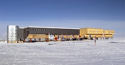 A long, large building consisting of several sections stands behind a line of flags flying on poles. The ground surface is ice-covered; in the middle foreground is a short striped pole which indicates the position of the South Pole