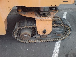 Small tracks on a roadworks machine. Note the rubber pads to reduce wear on the carriageway.
